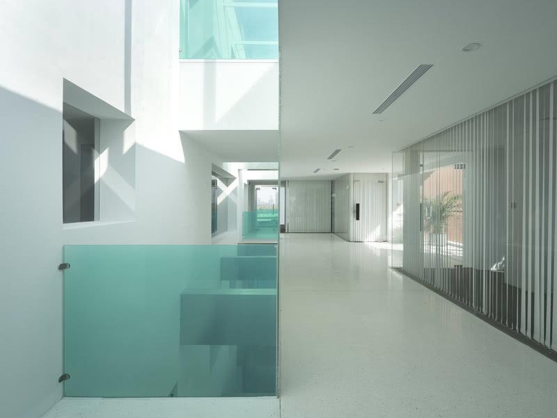每天各个时间的光照让玻璃扶手的绿色延伸至室内不同位置,地面与墙面大面积白色的运用让这一效果更为纯粹