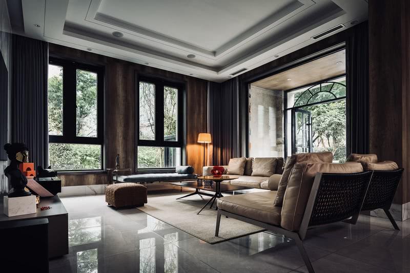 客厅运用了大面积的原木色家具,从地毯到沙发,都是不过分修饰、不过分渲染的天然本色,让整个空间显得静谧温柔。但朱红色的摆台、清透的红花瓶,却又悄然之间注入无无限的生机和活力。暖橘色的新中式立式台灯位于客厅一隅,既装点得整个房间充满温情,又不喧宾夺主,巧妙无比。三面落地窗外的绿色生机盎然,投射到客厅里来,整个房间仿佛都置于鸟语花香之中。