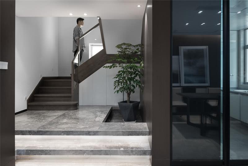 楼梯的初始位置是在进门处,设计师在楼梯前做了柜子设计,可以在视觉上起到缓冲作用,让空间层次递进,更为丰富。  楼梯下方设计师还做了凹槽设计,配合灯带,烘托温馨舒适的空间氛围,凹槽里放置绿植每次进门都能看到,让整个家更为清新自然,富有生机。