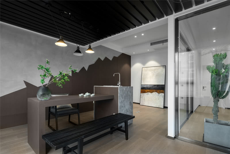 三楼楼梯口的房间,为配合业主的爱好,设计师设计了一间茶室,墙面用木饰面做出了山的造型营造中式韵味,与水泥漆配合,环保的同时更具艺术性。