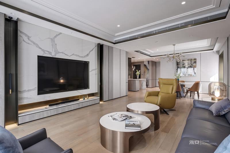 """在客厅的布置上,设计师的原则是""""宁简毋俗"""",原有的木纹地板面积过大不宜替换,因此在整体设计思路上,采用了灰色系为主色调进行调和降低饱和度。浅灰色的护墙板柔润且素雅,金属窄框线与空间结构线相互穿插、重叠、错落,线条流利而刚劲,在不同的角度又灵动地演变出不一样的情趣,给人含蓄的心灵愉悦,而非形色上的感官刺激"""