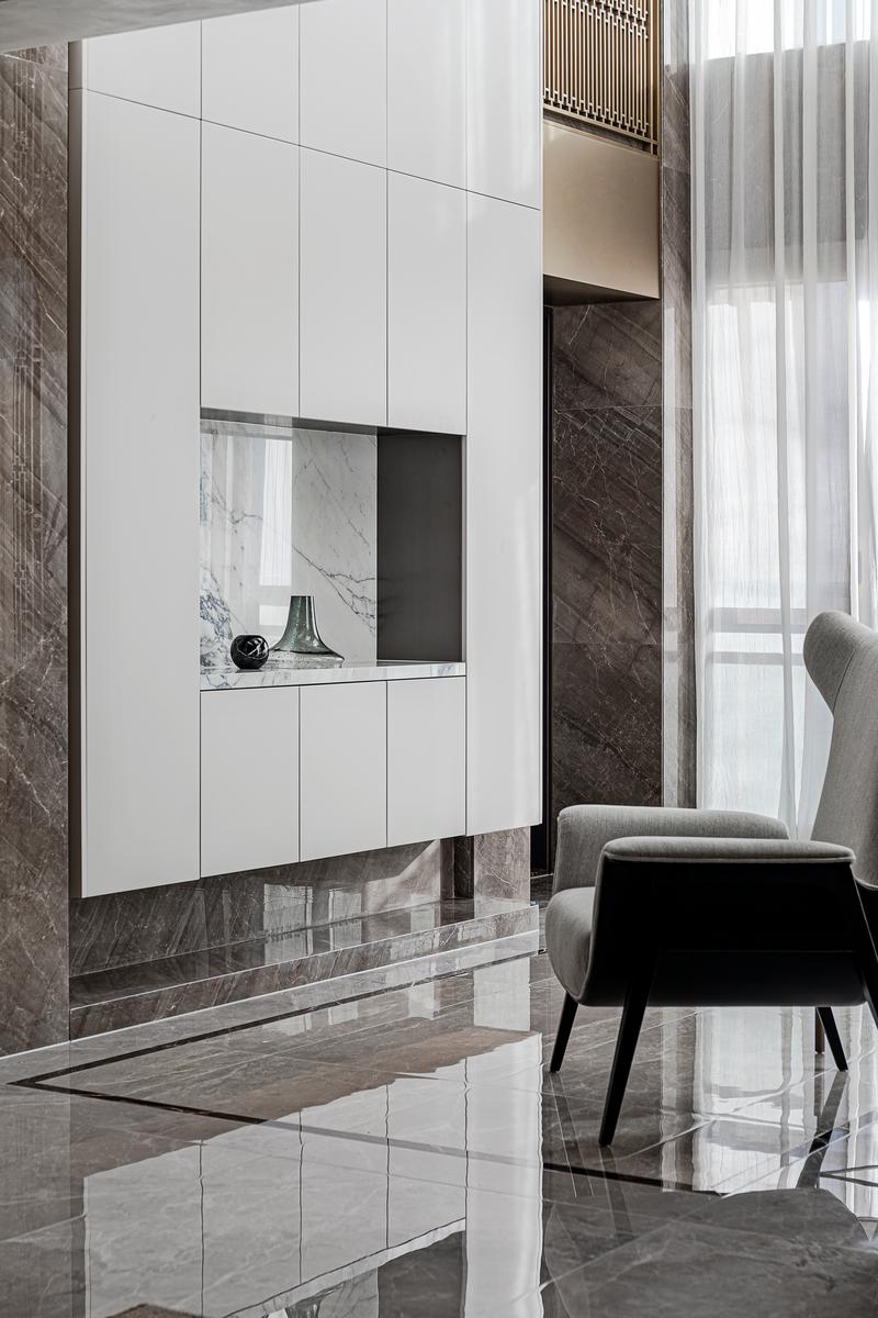 大面积留白的烤漆柜体,与造型屏风相互联结着,贯穿整个玄关空间,既雅致又不失生活气息。简约舒适的灰色休闲椅与个性小几的摆放也相得益彰,为空间增添几分细腻质感。