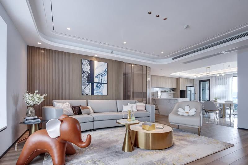 沙发与茶几,配合着光影与色彩的搭配,与背景墙的挂画一起组合成一幅现代主义的图景。周遭的浅木色调是对自然的归心逸致,家人闲坐,灯火可亲