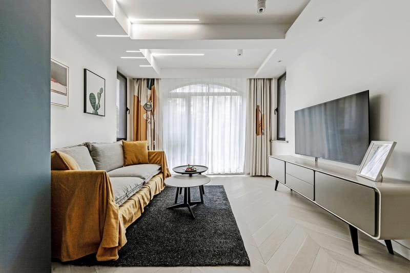 深灰色的地毯,浅灰色的沙发,白色的墙面,不同深浅色调的搭配让空间层次分明。暖黄色的加入能让原本冷酷的空间转换成为一个带有暖意、温馨的客厅。