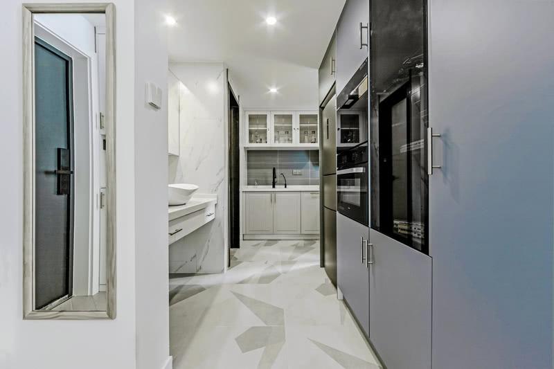 打破原始厨房和卫生间的格局,卫生间设计三分离,厨房设计开放式,充分利用过道一侧定制整体蓝灰色设备柜,嵌入式冰箱+设备柜+展示收纳柜。整体柜设计让空间更整洁大气有质感,同时延伸的柜体还可以作为玄关柜,避免进门看到客厅空间,起到很好视觉缓冲增加隐私。过道另一侧是卫生间干区台盆区。地面选择几何拼色地砖,拥有很好的视觉效果更方便清洁打理。