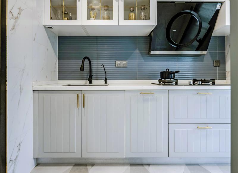 厨房一字型操作台面,整体橱柜白色为主,门把手金属色点缀增加一丝轻奢感。上面吊柜玻璃门更方便拿取厨具用品增加更多收纳。