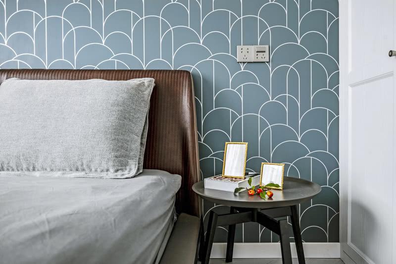 卧室床头背景墙采用灰蓝色壁纸,壁纸图案的设计有着纵深的视觉感,很时尚。床头选择黑色简约的边几代替床头柜,上面摆放装饰品,彰显主人精致的生活。