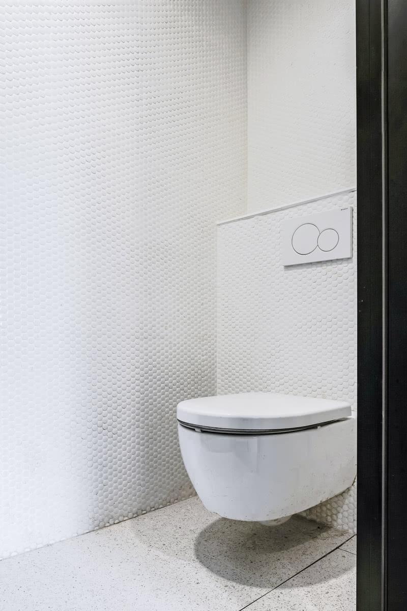 卫生间马桶区,墙面白色马赛克拼接设计,使得空间更高级精致,选择挂壁式马桶更轻巧更方便清洁打理。