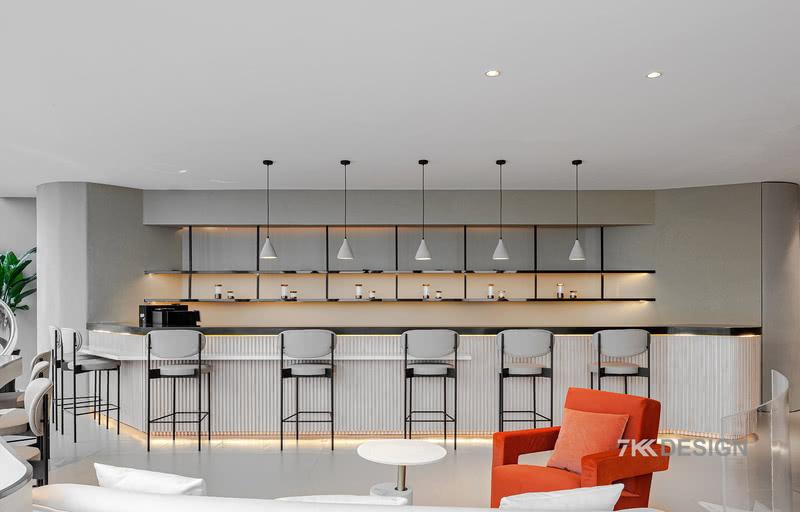 从玄关进来是开放的吧台区和休闲区,吧台以原木色为主,底下内藏灯带,营造轻盈通透的氛围。