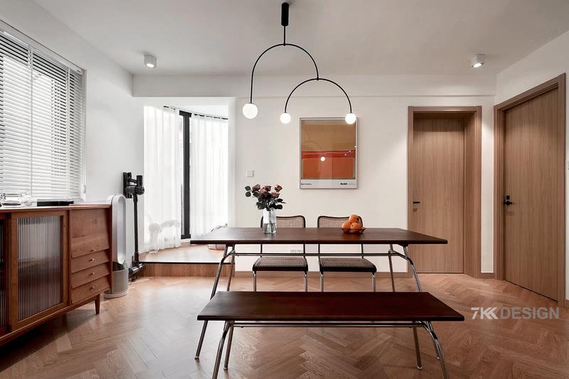 地面大面积人字拼地板拼接,增加视觉效果,挑选胡桃木餐桌椅延续北欧复古情调,座椅与条形椅、餐桌不同的高度搭配,丰富空间层次感。木色生香的家居氛围让人不由自主沉静下来,在这里无论是就餐还是办公,闲聊等都是十分惬意。餐厅后边阳台的空间抬高设计,是业主也比较喜欢的居心地,在这里呆上一小会,没事可以发发呆,放空大脑,什么都不去想,享受静谧的时光,还可以看到欣赏外面的景色。