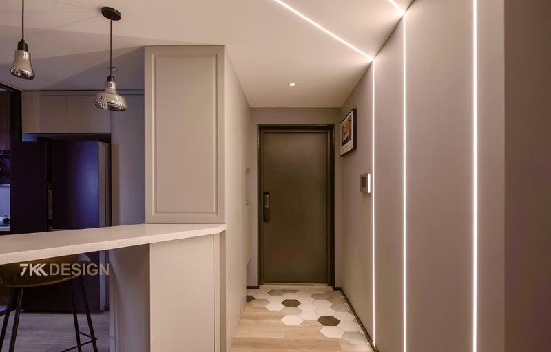 对于这套案子第1个改造的点就是进门之后的右手边,如何将原本厨房的区域对餐厅空间有一定空间感的支持,将墙体打掉之后,使得进门之后有收纳的空间,设计定制鞋柜方便进出使用。  入户玄关右边在设计了顶天立地定制鞋柜,中间留有镂空设计,方便业主进出门放置随身物品;地面黑白灰六角瓷砖+木地板拼接设计,时尚又个性;左侧的墙面和顶面做了内嵌灯带设计,给玄关增添光源的同时,科技感十足,整体看起来炫酷宽敞明亮。