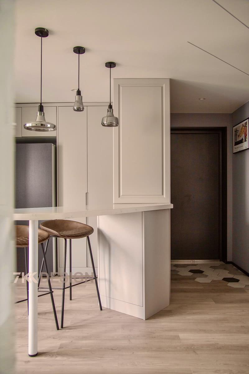 玄关往前走,则以左右分区设计。右侧为客厅,左侧做了倾斜吧台,用作客厅与厨房、餐厅隔断设计,同时也在视觉上延伸空
