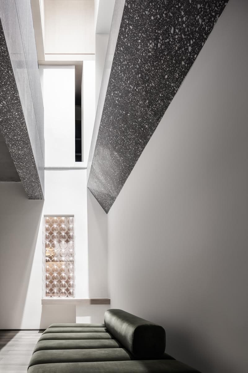 """正因有光的介入,明确而清晰的界限被柔和的光影所替代,视觉所能触及的温暖,让事物看似""""连在了一起"""",边界柔和而模糊。  此外,设计师通过建立垂直或悬浮的体块,在空间内形成了新的场域,并在这些体块的切面凿出一个个""""窗口"""",使不同空间的人可以在不同界面形成""""对望""""。"""