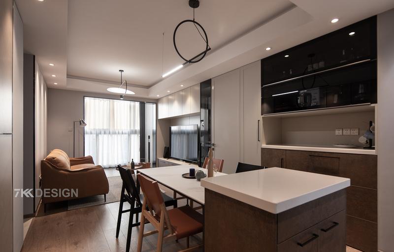 客餐区域相连,开阔的设计布局让人把整个公共区都尽收眼底。改造后的餐厅,以中岛+餐桌的形式重新布局,提升家的品质,也为他们之后的用餐方式提供更多的可能性。  餐边柜的设计,为了减少噪音中间采用了隔音棉。上柜选择玻璃柜门里面可以放置精美的装饰摆件,中间镂空可以放置常用的咖啡机、咖啡杯、茶具等,下柜放置餐具及日常物品。实用与颜值并存。