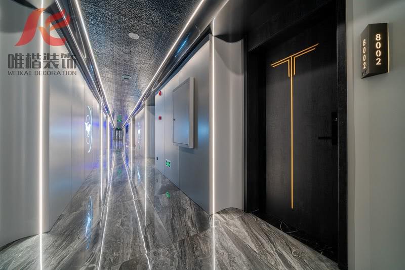 过道顶面采用水波纹不锈钢,金属质感体凹凸造型体现无限的延伸感,过道墙面灰色铝板经久耐磨易于打扫清洁,非常适合高密度人员来往经过的过道,局部穿插线型灯融入电竞科幻时尚感,门和门套使用黑色木纹实木面板,整个过道以黑白灰三原色基调为主打造简约时尚科技感。