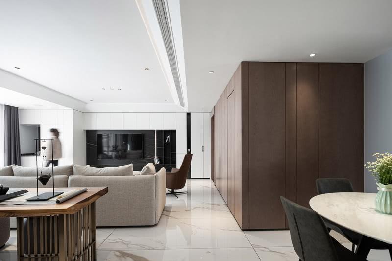 设计师在客厅公共空间采用了穿插的手法,让整个空间相互融合、能够互相沟通交流。在材质的选择上,电视背景墙、鞋柜、洗衣柜以大面积白色木饰面门板柜为主,局部透开,穿插金属材质开放柜,让空间更加灵动。