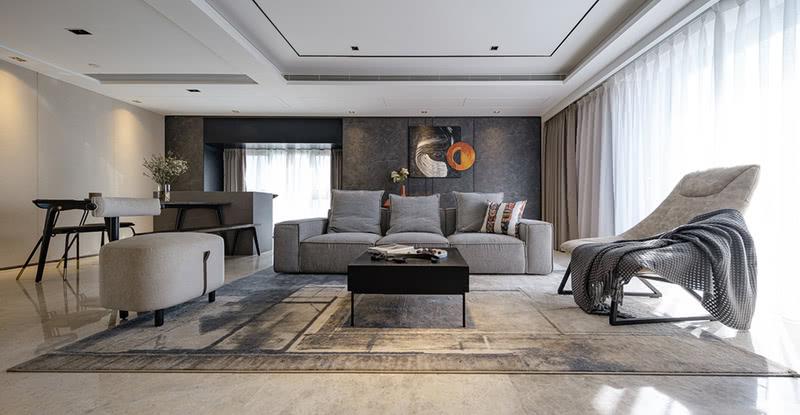 背景墙一面保留原有的暖米色硬包,另一面则换成了深色的木制石纹护墙板,搭配暖灰色布艺沙发、拼色抽象派地毯、深色木制家具等,流畅的线条比例与色块组合,展现出业主卓尔不凡的艺术品位。