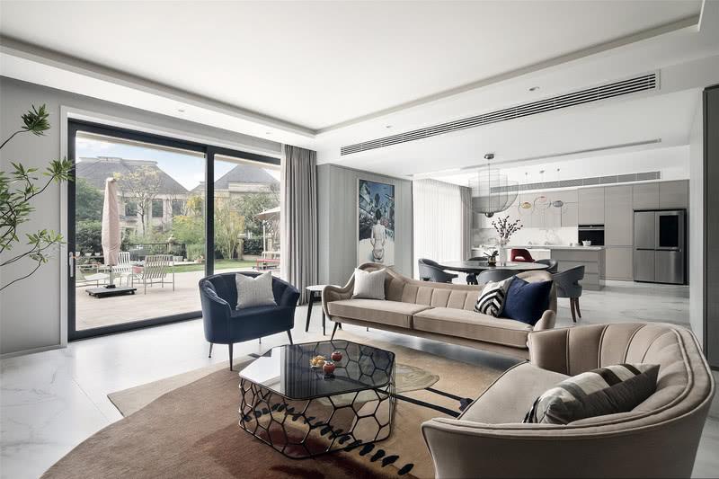整栋别墅坐落于高低起伏的坡路之间,在室内起居空间与室外地理环境的连接中勾勒出一种错落的美感。负一楼与户外花园相通,放眼望去,满眼葱郁。  整个项目的施工落地进行了三年之久。设计师对空间进行了合理的优化与改造,将清雅别致的家庭厅与简洁明快的西厨贯通一体,大气舒朗。自然光从门外肆意洒落进来,更增室内的开阔通透之感。墙上挂画艺术品来自王念东的《Hello City》,勾勒女性的自然线条,为空间添以艺术笔触。  净洁的厨餐厅开敞简约,MOOOI金属网编织的吊灯极具质感,仿若薄如蝉翼的花瓣聚拢绽放,托出中心的金色花蕊,营造出轻盈别致的姿态。业主在其间用自己亲手种植的自然新鲜的食材,来为家人做一顿可口的美餐,与家人一起分享种植的果实,不亦快哉。