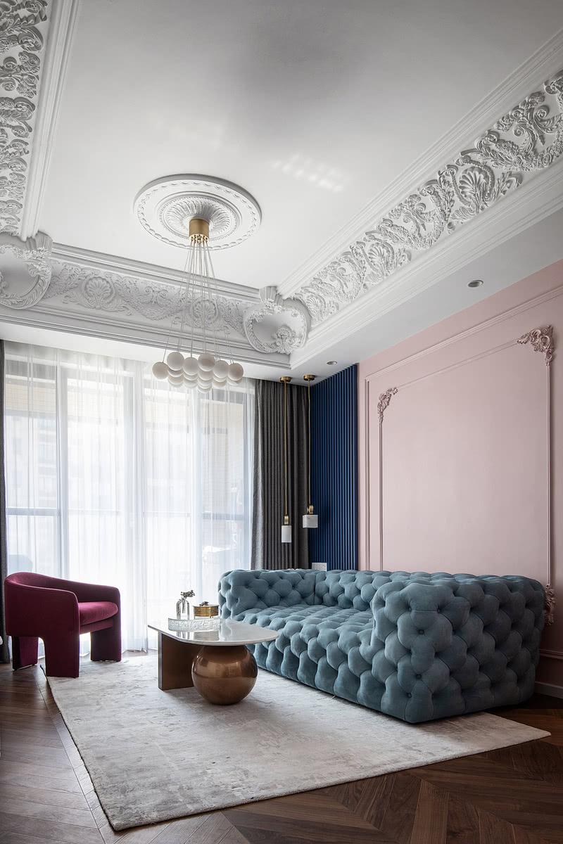 客厅设计大胆且富有创意,脏粉色和藏蓝色的撞色背景墙,搭配湖水蓝进口磨砂皮沙发和酒红色麂皮绒单椅,质感丰富又极有新意,色彩跳跃又相得益彰。