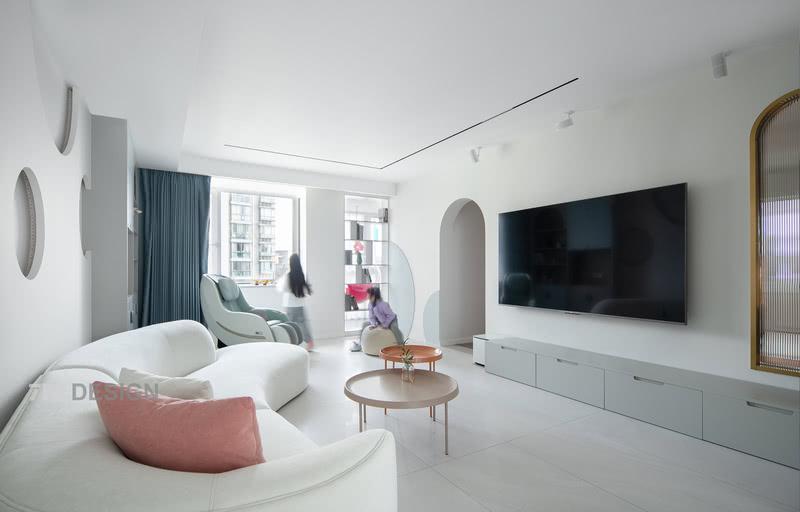 客厅整体是干净舒适的,颜色以白色和莫兰迪色系为主,打造了一个清新明亮的家。  从图中可以看到,设计师利用了很多圆形元素如:拱门,洞洞的沙发背景墙,弧形沙发,圆形茶几,是因为业主想要给孩子一个梦幻泡泡主题的家。