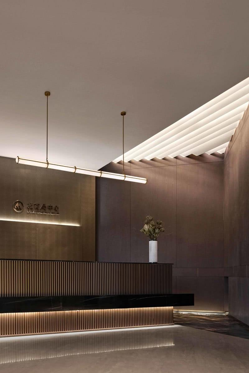 """入丨至臻之镜 前厅丨Lobby  设计的功能之一,在于""""再现""""空间,那些容易被忽略的艺术角落,那些使视线聚焦的景端,那些隐藏在空气中的分界...都唤醒着我们对美的感知,以入臻境。 大堂区,黑金色立柱与接待台整体的设计,大大加强了对石材的挑选。随之,我们被天顶的三角天光吸引着,便不自觉的走向——墙体角落。天顶仿天光与水纹理石互为呼应,喻示着源源流水,将流向更广阔的水境。"""