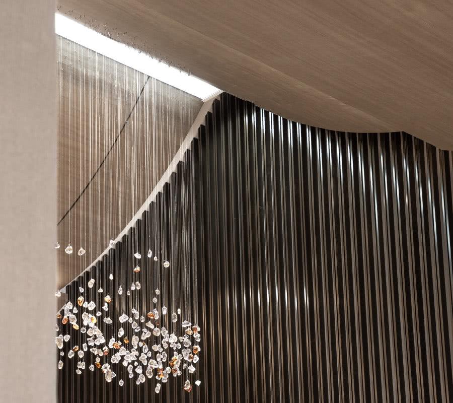 沙盘区上方的吊灯是由上千水晶石铺散而成,层次叠加,色彩和谐明亮,一直延伸至洽谈区,流动的造型感为整个空间注入新的灵魂。令人仰望的艺术世界,品咂不尽的悠悠情味。