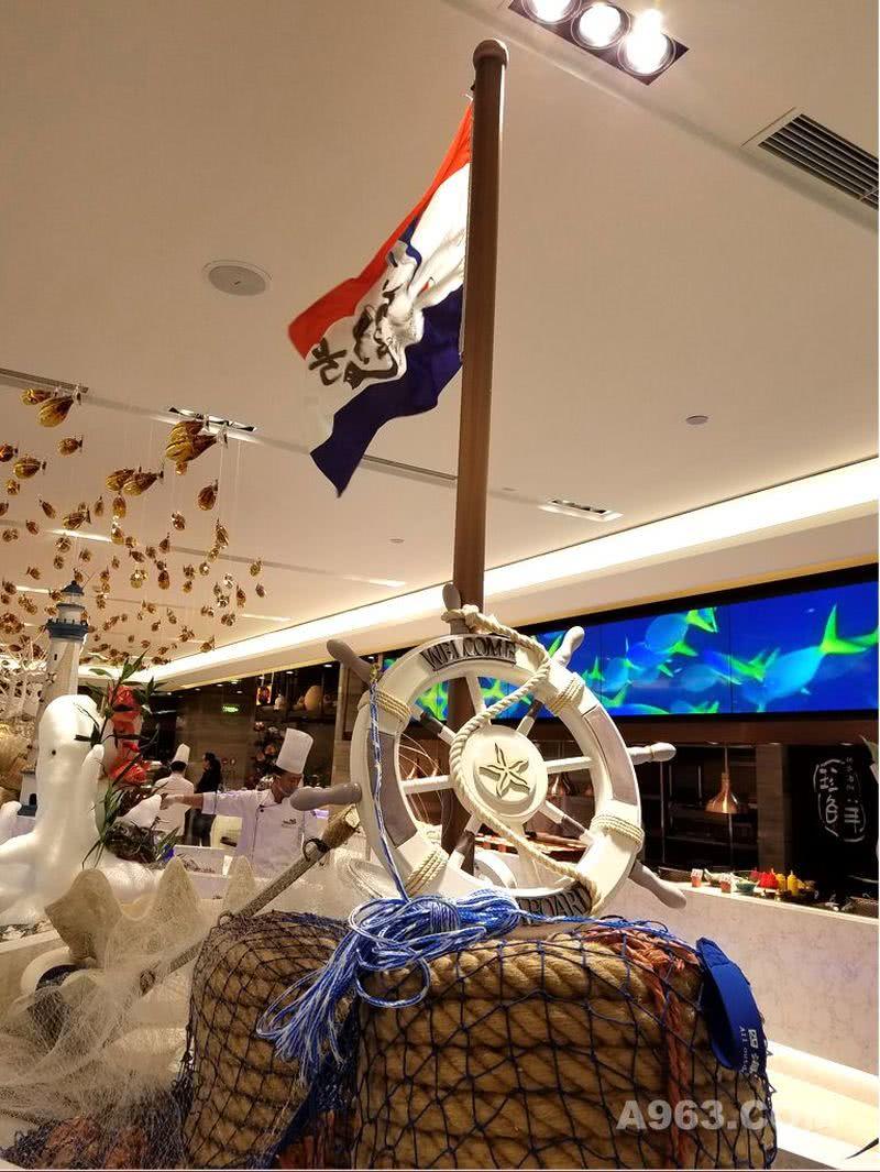这面带有企业LOGO旗帜,设立在初色餐厅的大自助餐区的一艘大冰船的上方,为了视觉效果更好,在旗杆端头设了出风口,这样就可以让旗帜一直飘扬起来,带有节奏和动感,让餐厅更显热情。